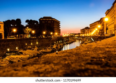 Picturesque view at sunset of the canal with boats within the city in the town Livorno, Tuscany, Italy.