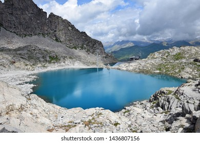 Picturesque view of turquoise blue Monticello lake at the Presena Glacier middle station towards Paradiso cableway, with Passo del Tonale mountain pass in background, summer trekking in north Italy