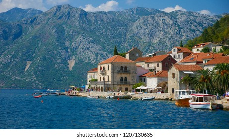 Picturesque view of the water of the Bay of Kotor and the church in the town of Perast. Historic buildings and beautiful wild nature attract many tourists and water sports enthusiasts here.
