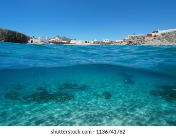 The picturesque village La Isleta del Moro on the seashore with fish and sand underwater, split view above and below water surface, Mediterranean sea, Cabo de Gata-Níjar, Almeria, Andalusia, Spain