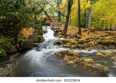 Picturesque waterfall in the Oliwa Park in autumnal scenery. Gdansk. Poland.