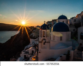 Picturesque white church with blue domes in Santorini over the sea at sunset