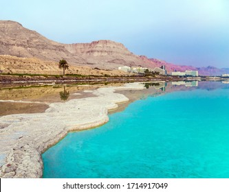 Picturesque white paths from evaporated salt. Early morning at the resorts of the Dead Sea. Azure sea water is full of healing salts. Israel. Concept of ecological, medical and photo tourism