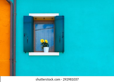 Picturesque windows with shutters and flowers on blue and orange wall of houses on the famous island Burano, Venice, Italy