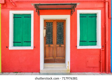 Picturesque windows with shutters of red house on the famous island Burano, Venice, Italy