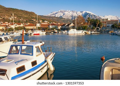 Picturesque winter landscape with small marina for fishing boats.  Montenegro, Bay of Kotor. View of Marina Kalimanj in Tivat city and  snow-capped mountains of Lovcen