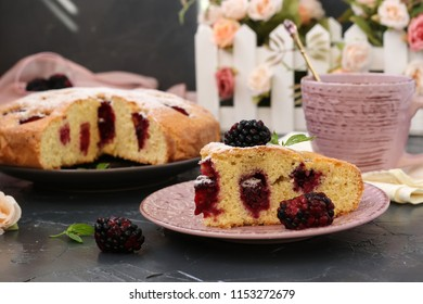 Pie with blackberries is located on a dark background. In the foreground is a piece of cake. In the photo there is a cup and a fresh blackberry.