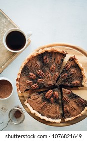 Pie with chocolate and pecan. Traditional baking for Thanksgiving. Top view, white background