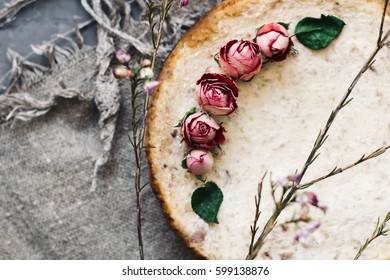 Pie from cottage cheese and bananas. Freshly baked cheesecake on  rustic background.  Decoration of dried flowers. Popular sweet dessert