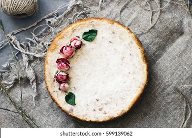 Pie from cottage cheese and bananas. Freshly baked cheesecake on  rustic background.  Decoration of dried flowers. Popular sweet dessert. top view