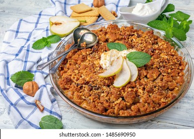 Pie crumble with pear, cinnamon, walnuts and natural yogurt in a glass baking dish on a white wooden table, selective focus.