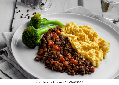 Shepherd's pie made of smashed potatoes, minced meat, lentil and vegetables on a white wooden table. Classic meat pie.