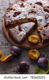 Pie with plums and fresh plums on wooden table. Homemade trditional food