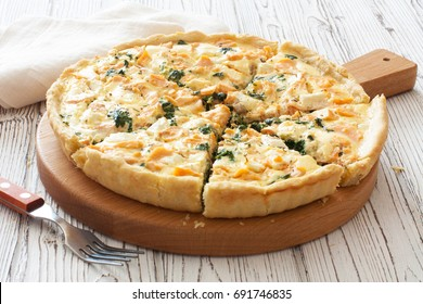 Pie ( quice) with salmon, spinach and soft cheese on a white wood background