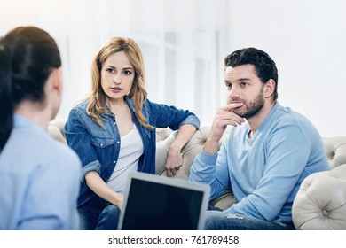 Piece of advice. Nice pleasant young couple looking at their therapist and listening to her while trying to cope with their problems