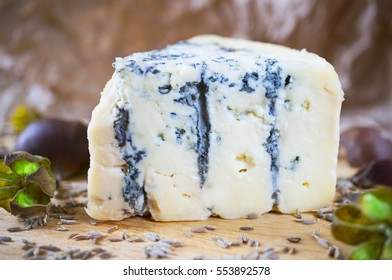 A piece of an amazing fresh blue cheese on a wood board.