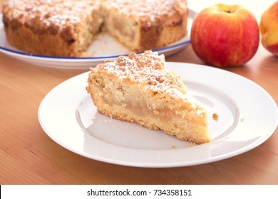piece of apple pie with crumbles on wooden ground