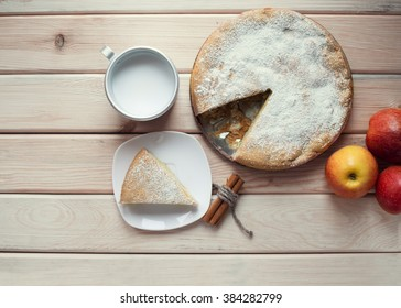 A piece of apple pie and cup of milk on a wooden table. Apple pie, cinnamon sticks and red juicy apples. Top view.
