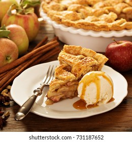 Piece of an apple pie with ice cream scoop and caramel sauce on a plate, fall baking concept