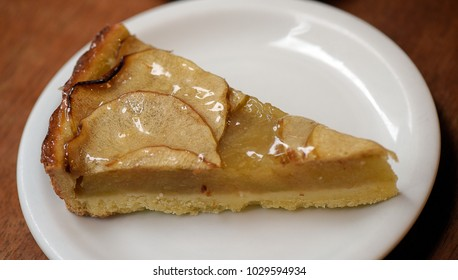 Piece of apple pie, on white plate on wooden table