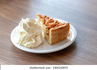 A piece of apple pie on white plate served with whipping cream on the side, Homemade apple pie on wooden table, Freshly baked.
