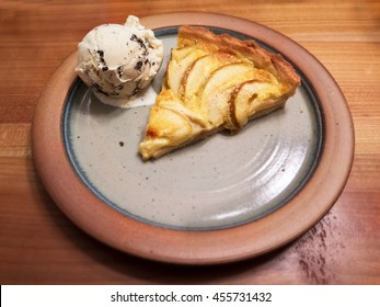 Piece of apple tarte with ice cream on a rustic plate from above