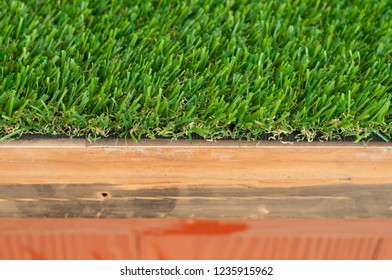 Piece of Artificial grass on wooden table. Artificial turf. Green plastic grass