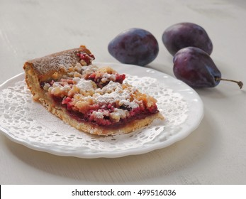 A piece of Bavarian plum pie on white plate. Selective focus.
