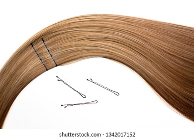 Piece of beautiful, shiny blonde hair on white isolated background with bobby pins. Wavy shape