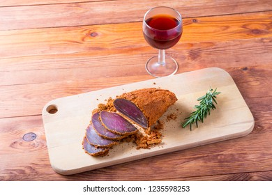 A piece of beef basturma and a glass of wine on a wooden table