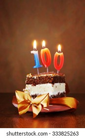 Piece of Birthday Chocolate Cake with Burning Candle as a Number One Hundred on Brown Background