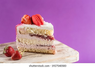 A piece of biscuit cake with strawberry filling and fresh strawberries on a wooden stand on a bright purple background. Close-up with a copy space for the text. Dessert for a holiday and birthday.