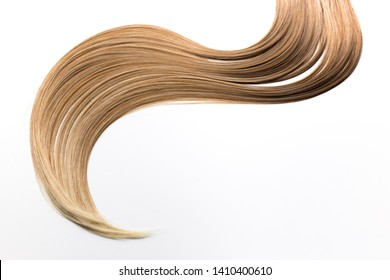 Piece of blonde hair on white isolated background. Wavy shape. Hair care, healthy hair