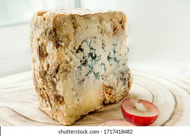 A piece of blue Stilton cheese on a wooden antique background with large red grapes. Close up.