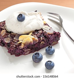 Piece of blueberry and chia seeds pudding or cake, on a plate. Served with whipped cream
