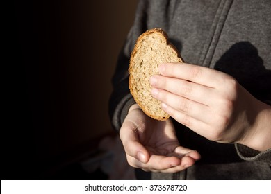 Piece of bread in children hands. Hunger and helping concept.