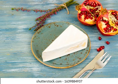 Piece of brie light cheese on blue wooden background. Studio Photo