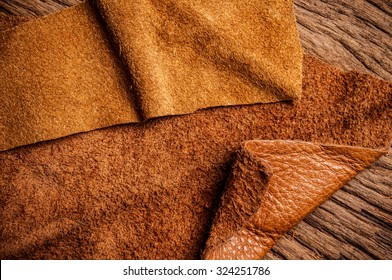 Piece of Brown Leather and Suede Cut on Wood Table Workspace. Concept and Idea of Fine Leather Crafting, Handmade, Handcrafted and Leather Works. Background Textured and Wallpaper. Rustic Style.