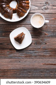 A piece of Bundt cake with chocolate icing and a cup of hot coffee on a wooden background. Top view.