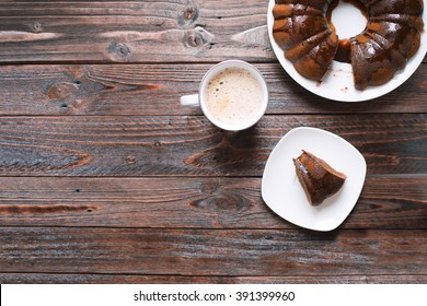 A piece of Bundt cake with chocolate icing and a cup of hot coffee on a wooden table. Top view.
