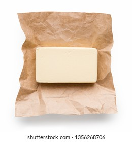 Piece of butter in craft paper on white background, top view