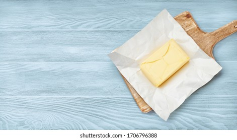 Piece of butter on package paper and wooden board. Top view of butter on blue wooden background.