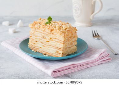 Piece of cake Napoleon on blue plate on pink textile. Russian cuisine, layered cake with pastry cream, close up view
