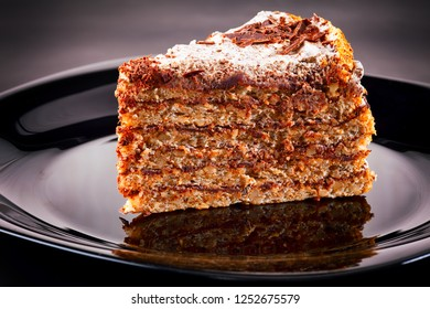 Piece of cake on black plate. Black background.
