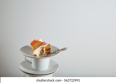 Piece of cake on small ceramic saucer next to silver dessert fork, isolated on white