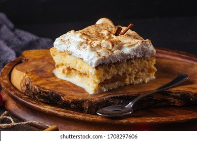 Piece of cake three milk prepared at home. The image is made on a dark background and rustic boards. Latin American dessert
