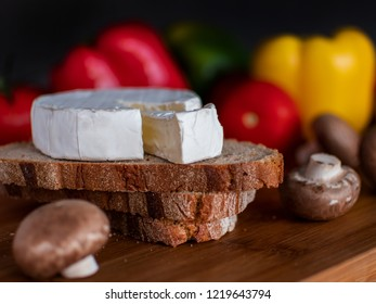 Piece of camembert on bread with vegetables as decoration on the table