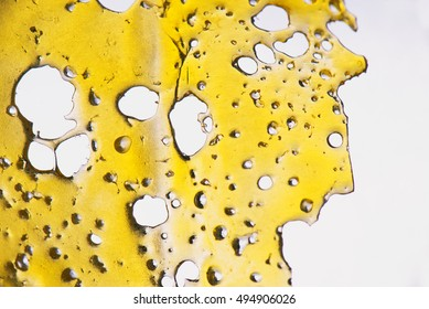 A piece of cannabis oil concentrate aka shatter isolated against white background