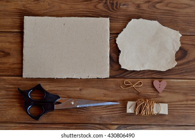 A piece from a cardboard box, torn piece of wrapping paper, scissors, waxed cord, a bow, a heart shaped wooden button. Set of materials for children creativity. Paper cutting arts and crafts for kids