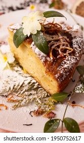 A piece of Charlotte is decorated with orange peel and powdered sugar